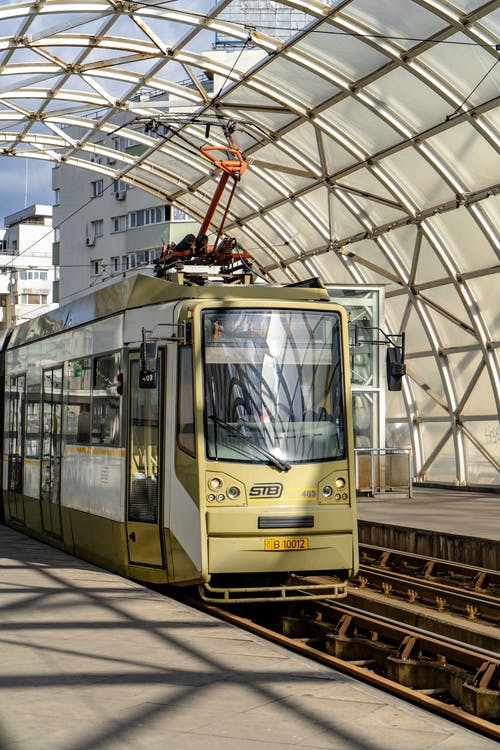 Tram on railway station under arched ceiling