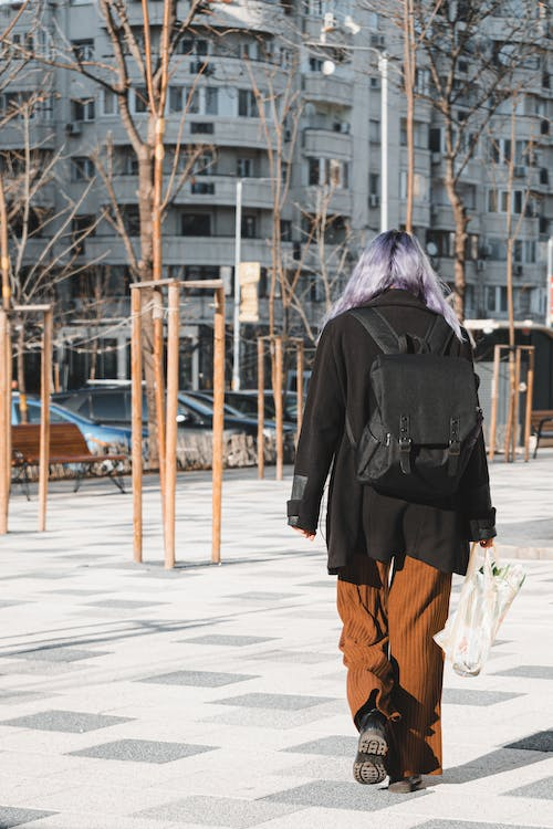 Back view full body of unrecognizable female with bright dyed long hair strolling in park with paved ground and bare trees