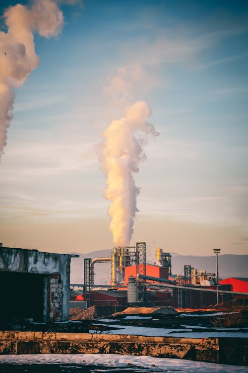 Industrial factory emitting toxic fume into air and polluting environment in rural area in winter