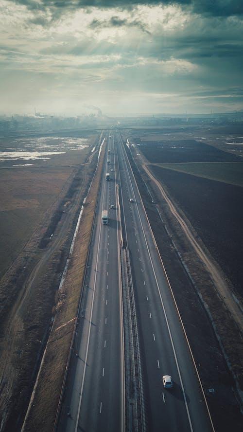 Cars driving on straight asphalt road between fields