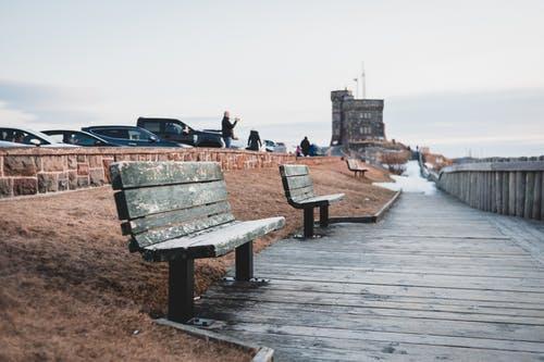 Wooden footpath with old benches near tower at sunset
