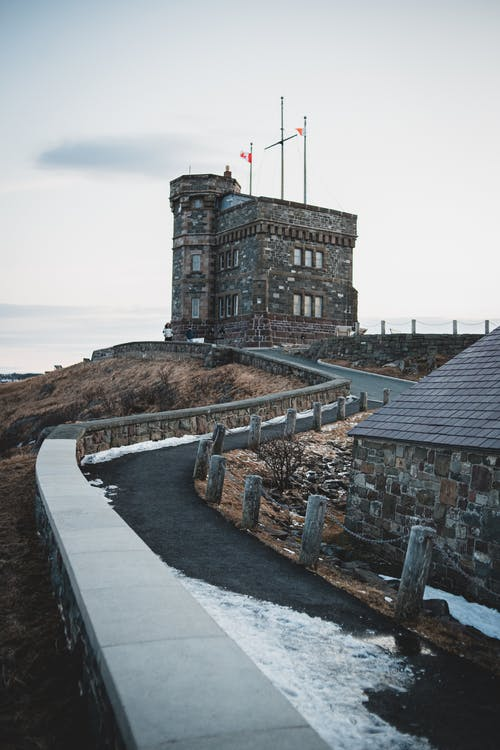 Asphalt sidewalk curve covered with snow leading to medieval Cabot tower with flags in province of Canada on winter day