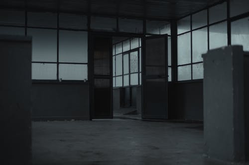 Interior of spacious empty room of gloomy abandoned building with glass windows and opened door
