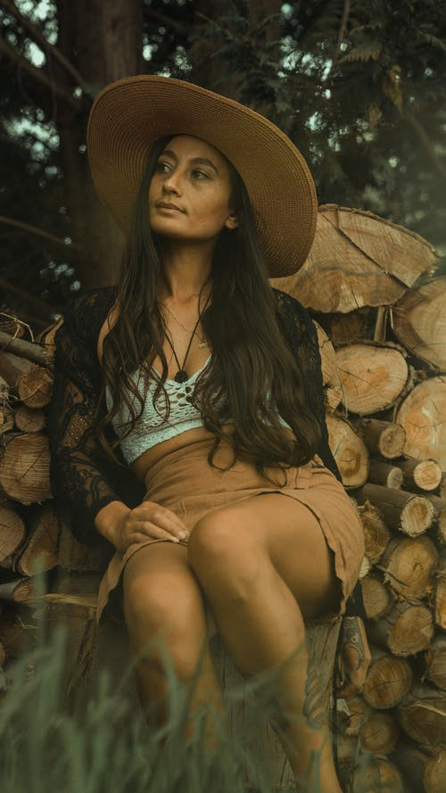 Woman in Blue and White Floral Shirt and Brown Sun Hat Sitting on Brown Wood Log