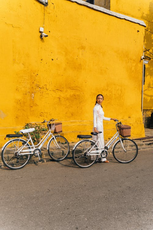 Ethnic woman standing with bicycle in city