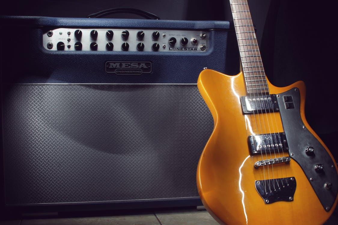 Brown Electric Guitar Beside Black Guitar Amplifier