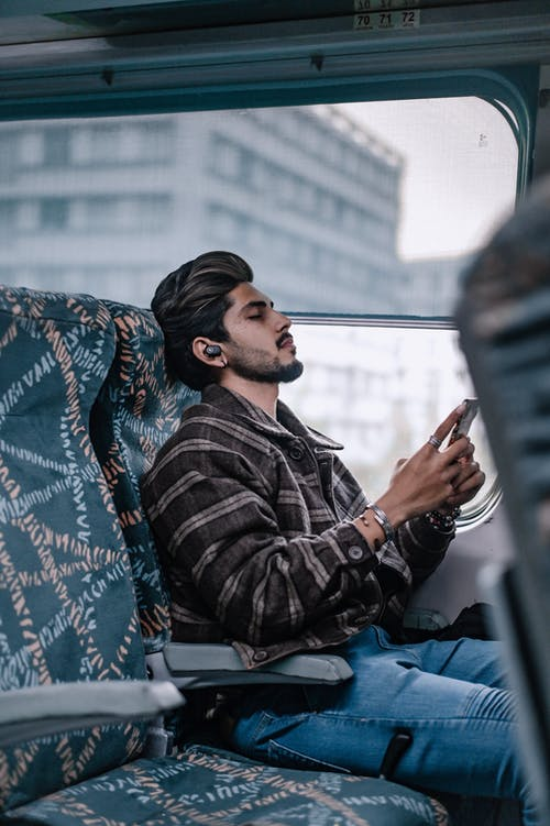 Bearded Man Sitting inside a Bus Listening to Music