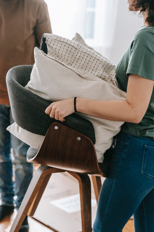 Woman Carrying Chair With Cushions