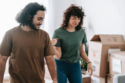 Man in Brown Crew Neck T-shirt Standing Beside Woman in Green Crew Neck T-shirt