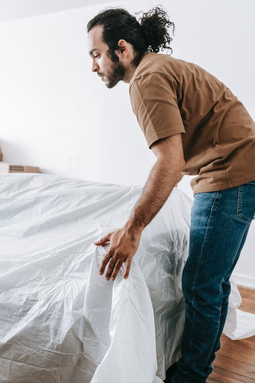 Man Covering A Couch With Linen