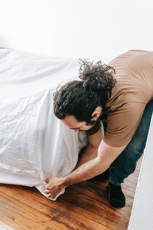 Man Covering The Couch With White Linen