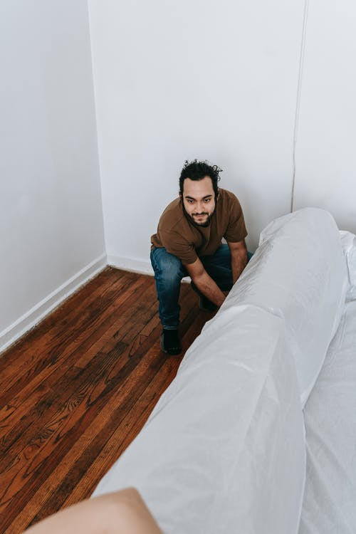 Man Covering A Couch With White Cloth