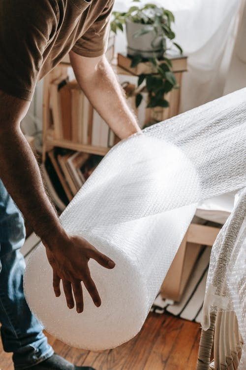 Person Holding A Roll Of Bubble Wrap