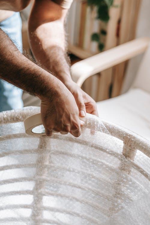 Person Wrapping A White Wooden Chair