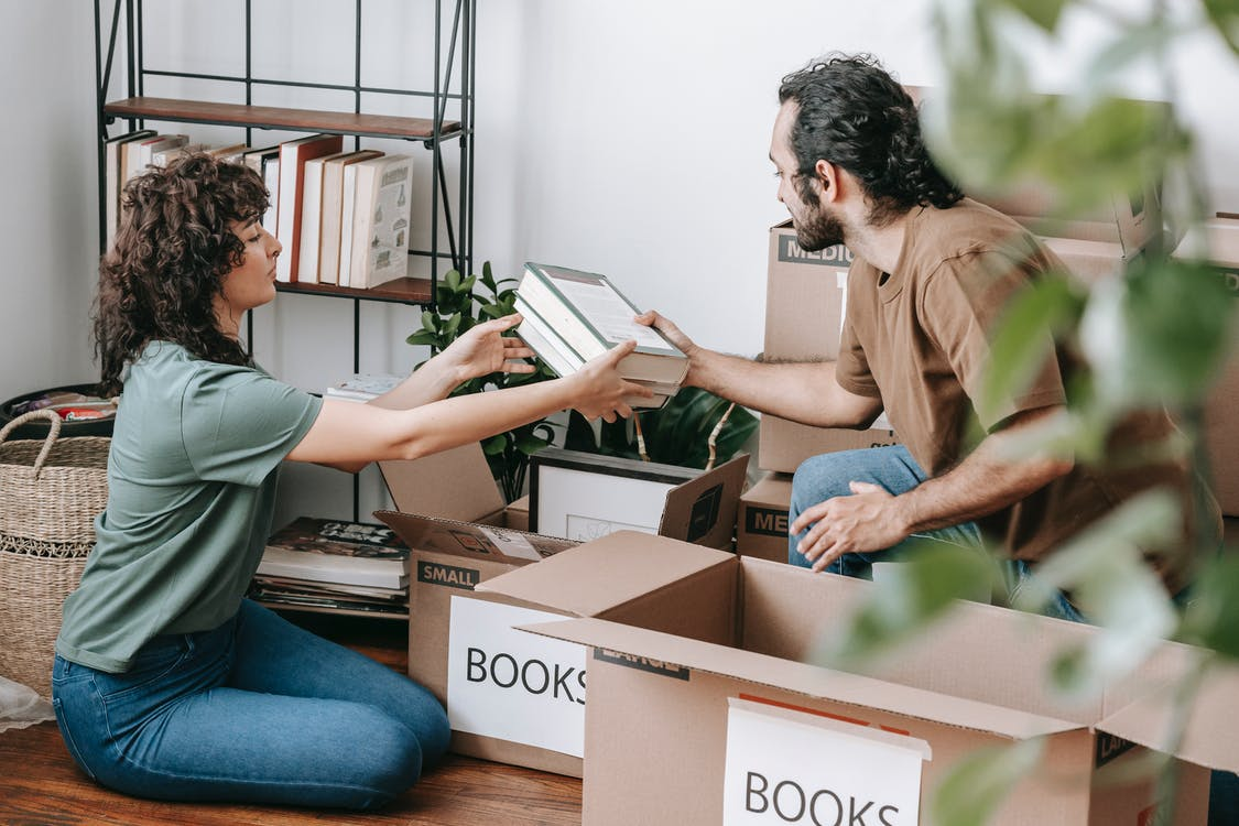 Couple Packing Books In A Box