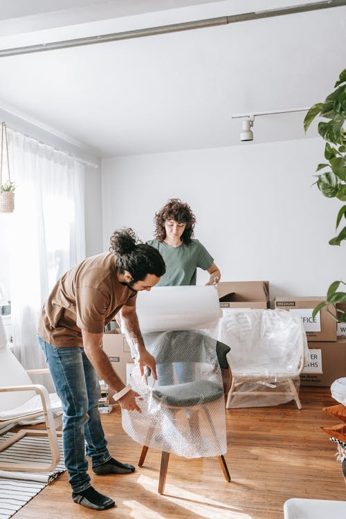 Couple Wrapping A Chair With Plastic