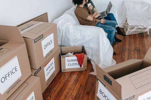 Couple Sitting On A Couch Near Brown Boxes
