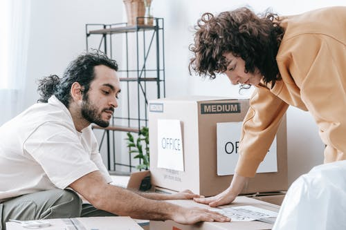 Couple Putting A Label On Box