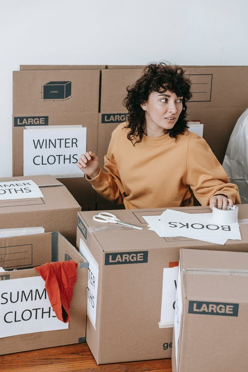 Woman Putting Labels On Boxes