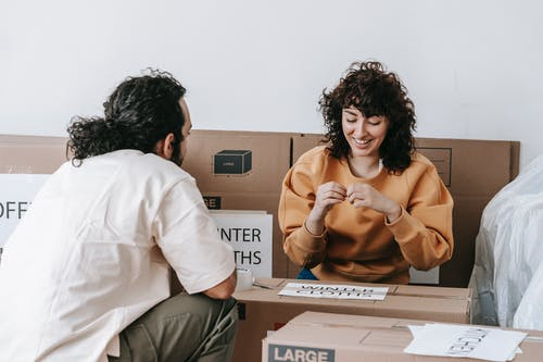 Couple Sitting Beside Boxes With Labels