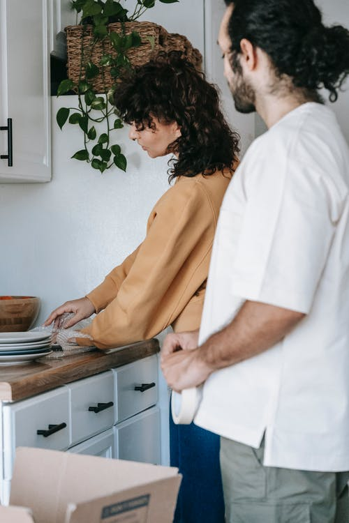Woman Wrapping Up Plates In The Kitchen