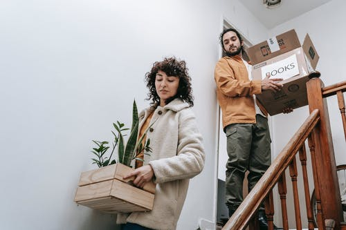 A Couple Moving Out Carrying A Box And Crate With Plants