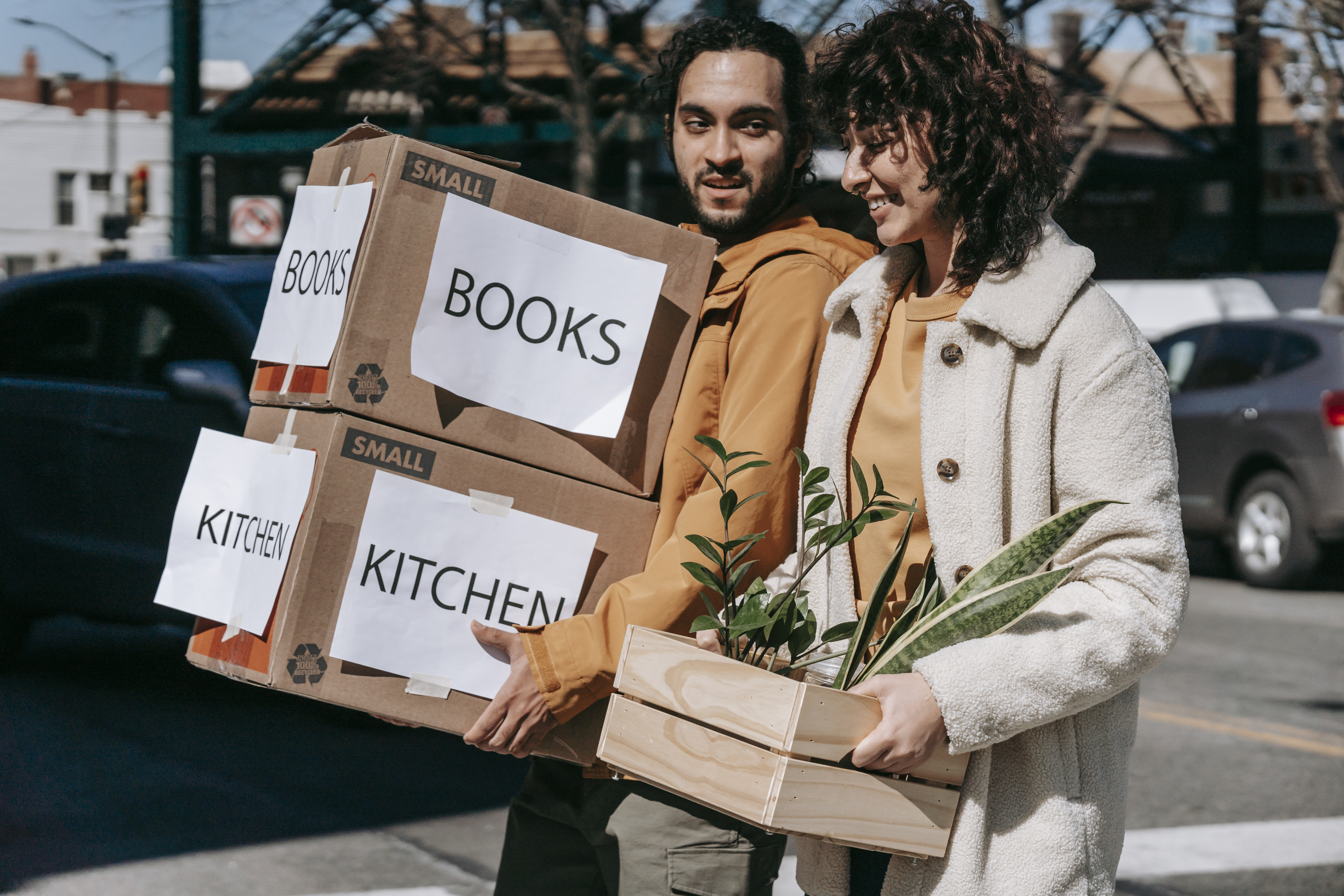 man carrying boxes and woman holding a box of plants