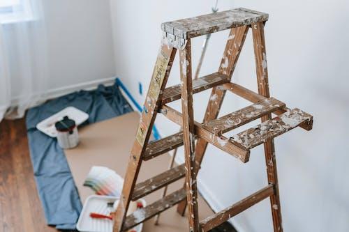 A Dirty Brown Wooden Stepladder Inside A Room