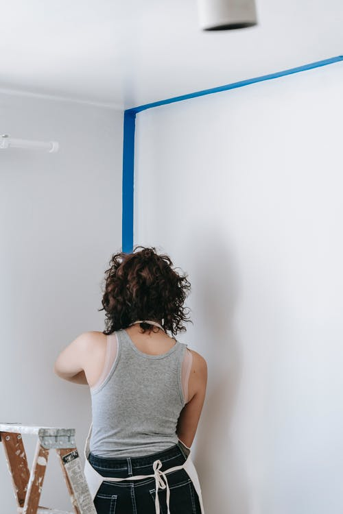 Back View Of Woman Putting Tape On Wall