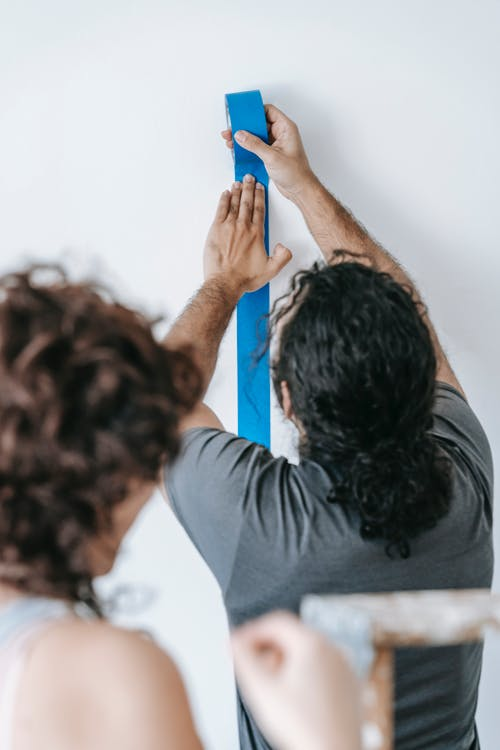Man in Gray Shirt Putting Tape On Wall