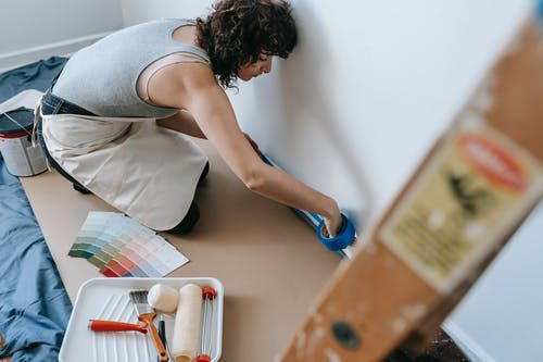 Woman Putting Tape On Wall