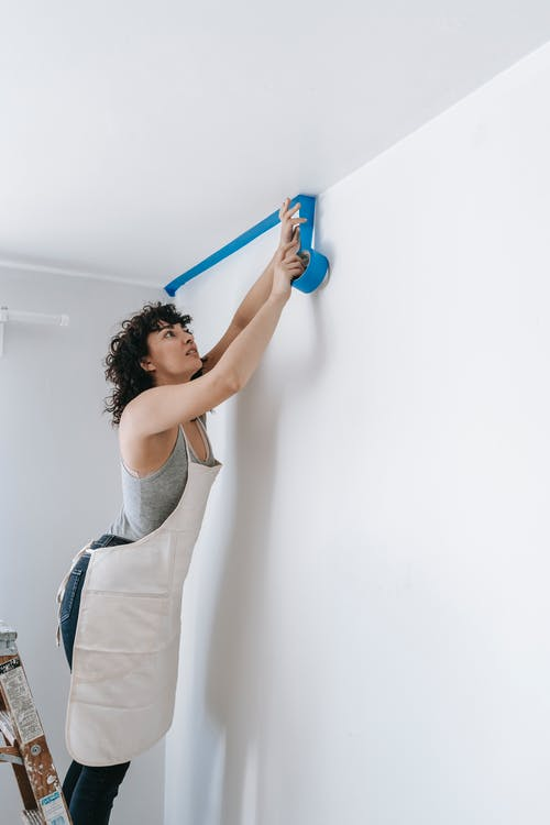 Woman In Her Work Clothes Putting Tape On Wall