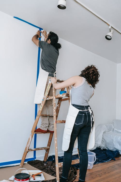 Man Putting Tape On Wall With Woman Holding The Stepladder