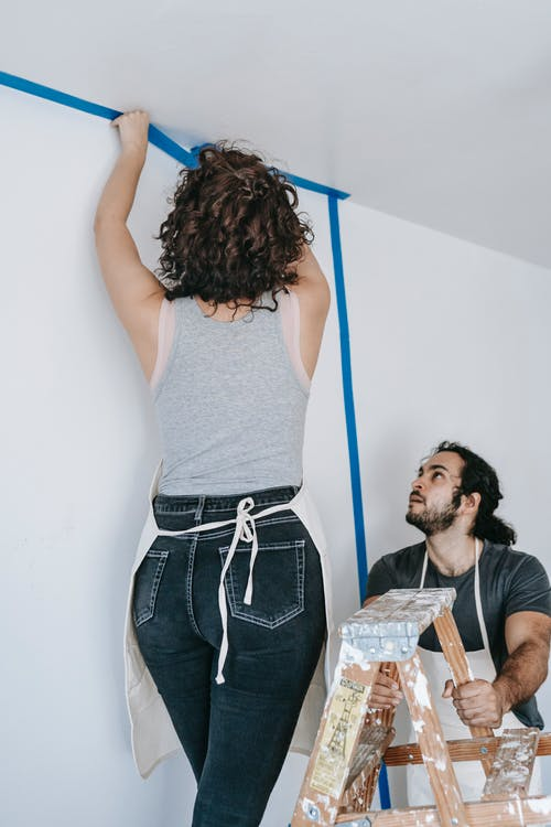 Woman Putting Adhesive Tape On Wall