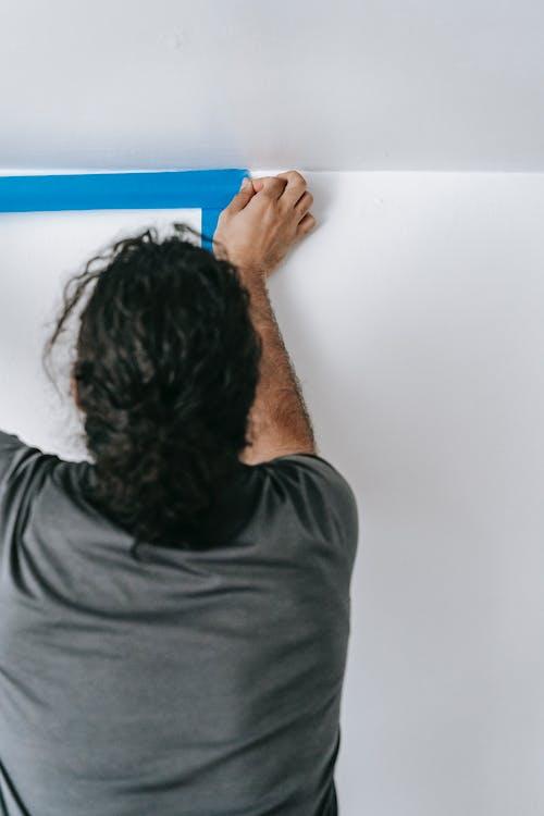 Man Putting Adhesive Tape On Wall