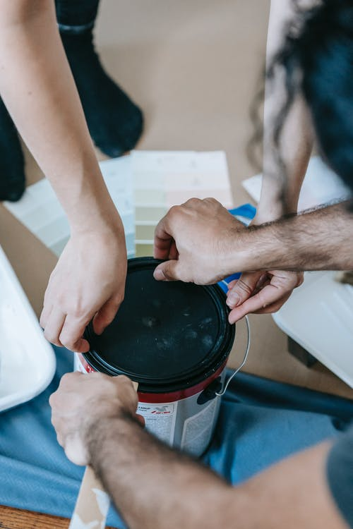 Two People Opening A Can Of Paint