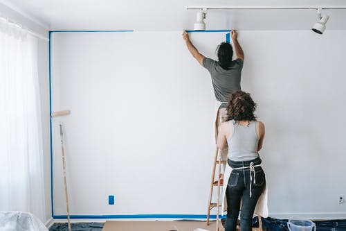 Man Standing On A Stepladder Putting Tape On Wall