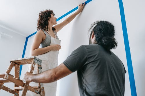 Man Standing Beside Woman On A Stepladder Painting The Wall