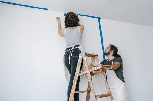 Woman On A Stepladder Painting A Wall