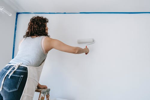 Woman On A Ladder Painting A Wall
