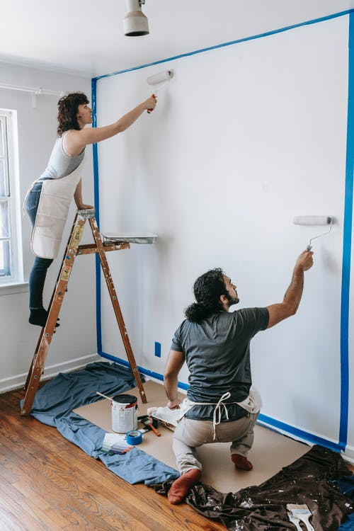 A Couple Painting The Wall