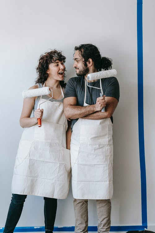 Couple Standing By The Wall With Paint Rollers
