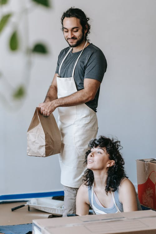 Man Holding A Paper Bag Near A Woman Sitting On Floor