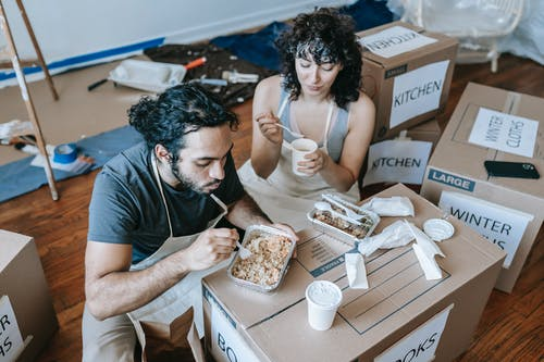 Couple Eating With Food On A Packed Box