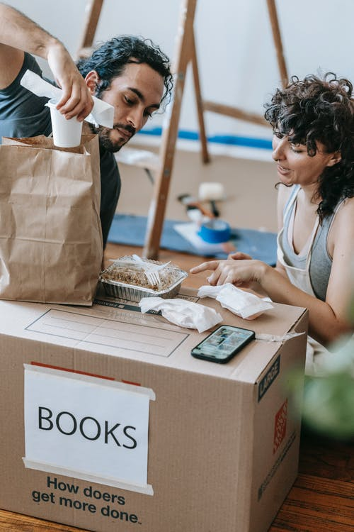 A Couple With Food On A Box Of Books