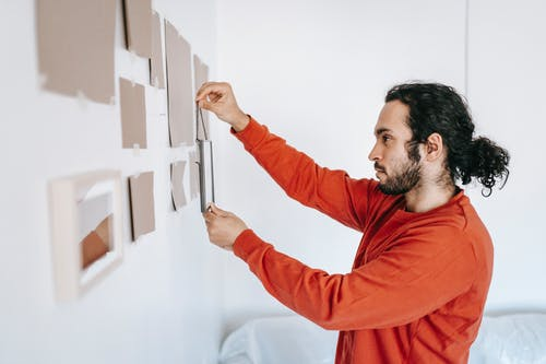 Man Putting Frame On Wall