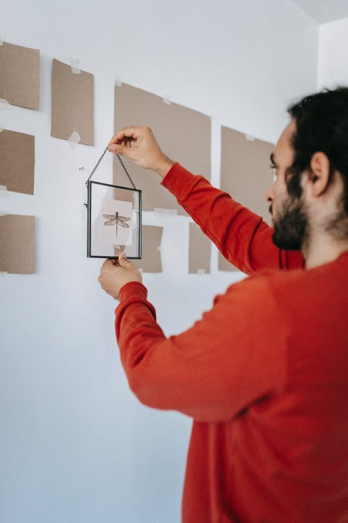 Man Hanging A Frame On Wall