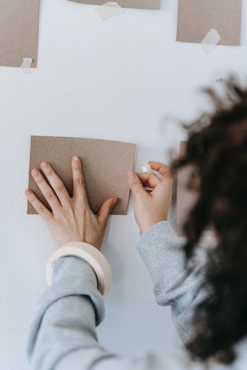 Crop woman sticking cardboard sheet on wall in house