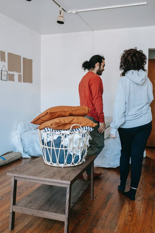 Couple Standing In A Room Beside Packed Things