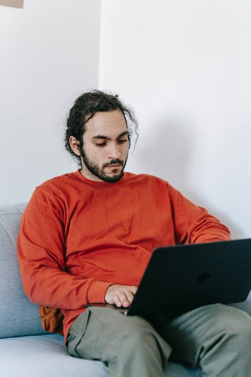 Man in Red Sweater Using Black Laptop Computer